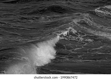 A grayscale shot of a wave of the sea