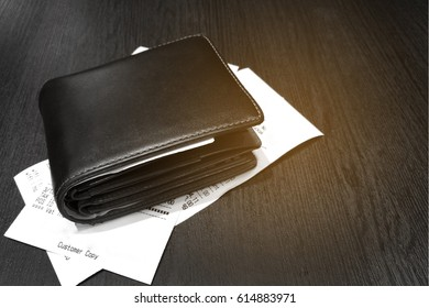 Grayscale tone of Money and credit card in a leather wallet on wooden table and bill slip with sunshine background