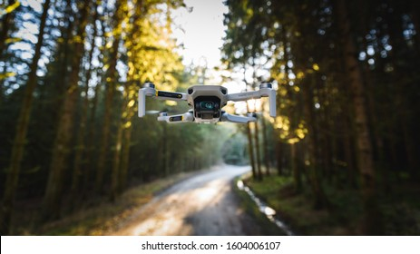 Graz, Austria: 02.01.2020 - Close up shoot of a DJI Quadcopter Drone Mavic mini 249g. Drone flying in sunny forest. DJI is the market leader in drones and aerial photography systems.