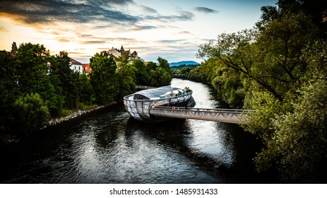 Graz, Austria - 17.08.2019: View at Mur river, Murinsel on bridge, people enjoy beautiful summer. Travel destination.