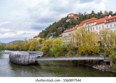 GRAZ, AUSTRIA - April 13 2012: The artificial island and bridge of a futuristic architecture style made of steel and glass on the Mur river in Graz. It is a famous landmark and a tourist attraction