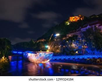 Graz, Austria - August 22,2010: Scenic nightscape of Murinsel bridge on River Mur and illuminated castle in Graz, Austria.