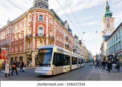 Graz, Austria - February 16, 2019: Tram and people on Herrengasse Street in Downtown and Old city of Graz in Austria. Town in Styria in Europe. Travel and history with architecture.