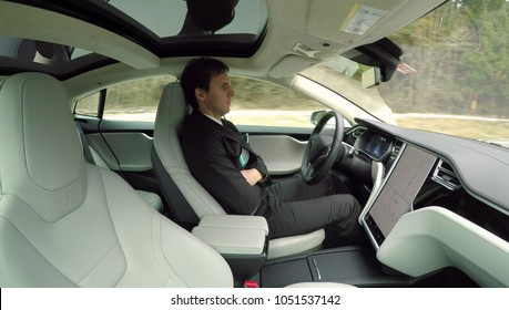 GRAZ, AUSTRIA - FEBRUARY 2nd 2017: Businessman on business trip traveling in new luxury autonomous self-driving autopilot Tesla Model S driverless car. Electric vehicle driving on highway by itself