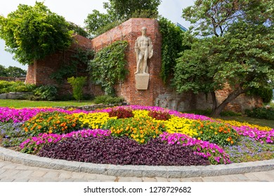 GRAZ, AUSTRIA - JULY 2018 : Sculpture titled Furchtlos und treu, meaning Fearless and faithful, on fortress wall above colorful flower bed at Schlossberg Castle Hill in Graz, Austria on July 20, 2018.