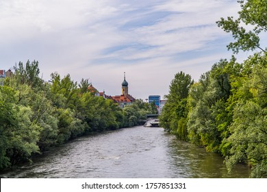 Graz, Austria - June 16, 2020 - the Mur river lined by trees with a church tower and buildings in the background on a cloudy day