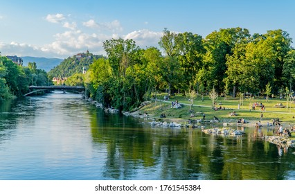 Graz, Austria - June 22, 2020 - people relaxing and sunbathing in the Augarten park on the banks of the river Mur with the Schlossberg (castle hill) in the background