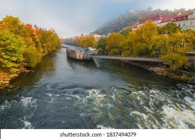 Graz, Austria- October 18, 2019: Mur river in autumn, with Murinsel bridge and old buildings in the city center of Graz, Styria region, Austria.