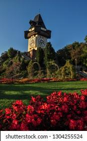 GRAZ/ AUSTRIA SEPT 2016: The medieval Clock tower Uhrturm in flower garden on Schlossberg hill, Graz, Austria