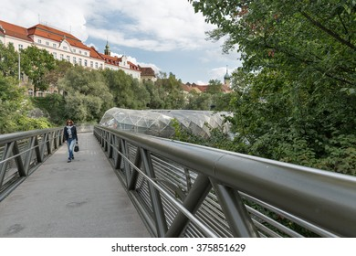 GRAZ, AUSTRIA - SEPTEMBER 11, 2015: People walk on the artificial island on the Mur river, called Murinsel, designed by American architect Vito Acconci and built for the European Cultural Capital 2003