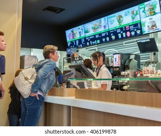 GRAZ, AUSTRIA - SEPTEMBER 12, 2015: people make an order in McDonald restaurant. McDonald is the world's largest chain of hamburger fast food restaurants founded in the United States.
