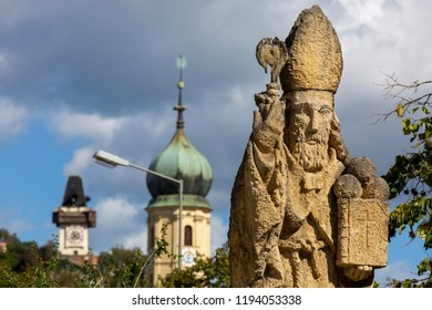 Graz, Austria - September 25, 2018 : Statue of St. Nicholas on Nikolaiplatz square in the city of of graz.In the background church franziskanerkirche and clocktower on schlossberg hill
