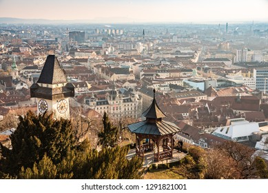 Graz, Styria / Austria - 20.01.2019: View at Graz City from Schlossberg hill, City rooftops, Mur river and city center, clock tower Sun on the winter blue sky. Travel destination.