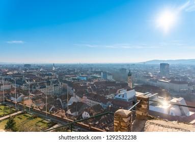 Graz, Styria / Austria - 20.01.2019: View at City Graz from Schlossberg hill, city center, clock tower, river Mur, Sun on the winter blue sky. Travel destination.