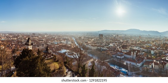 Graz, Styria / Austria - 20.01.2019: Wide panorama of Graz City, City rooftops, Mur river and city center, Schlossberg hill and clock tower Sun in winter, blue sky. Travel destination.