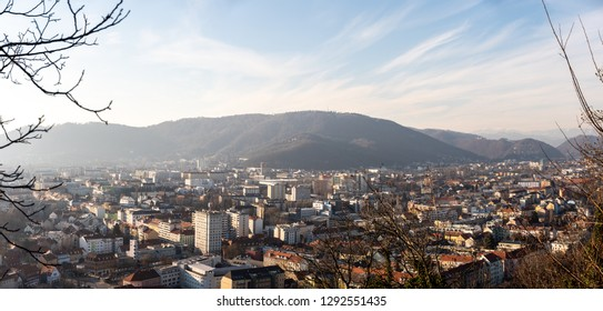 Graz, Styria / Austria - 20.01.2019: Wide panorama of Graz City, City rooftops, residential area, mountains in background Sun in winter, blue sky. Travel destination.