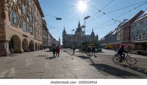 Graz, Styria,Austria - February 25, 2018: passersby und biker on main square with townhall graz, austria