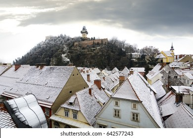 Graz winter scene with clock tower and snowy rooftops