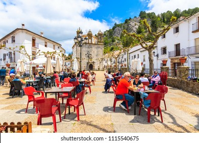 GRAZALEMA TOWN, SPAIN - MAY 12, 2018: Tourists eating lunch on church square in typical Andalusian village of Grazalema which is one of most visited white towns in Southern Spain.