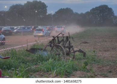 Grazie, Italy - 08.17.2019: An old plow for working in the field, on the left is a parking lot for cars. Very dusty field due to the demonstration of the work of tractors, evening. Feast of Ferragosto