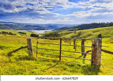 Grazing hill sides surrounding Lake Lyell on Coxs river in Australian Blue Mountains country. Entry gate to the green pasture under warm sun light.