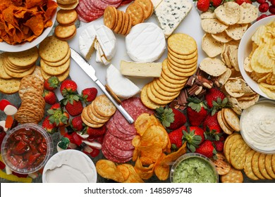 A grazing table filled with cheese, crackers, strawberries, salami, chips, dips and other fresh food for entertaining.