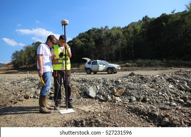 GRDELICA, SERBIA - AUG 14 2014: Two land surveyors watch controller screen while measuring point using GNSS rover mounted a pole, on a road construction site near Grdelica, Serbia on August 14, 2014.