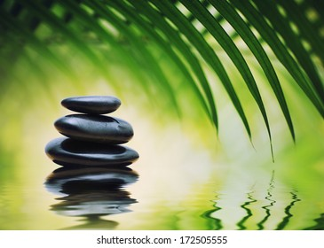 Grean bamboo leaves over zen stones pyramid reflecting in water surface