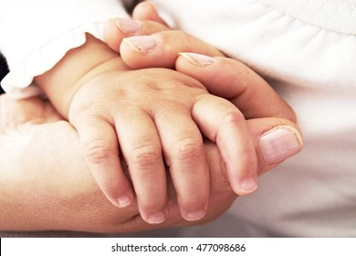 Greast hand grabbing the hand of her baby