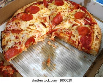 greasy american deep dish pepperoni pizza in a box