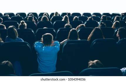 great ammount of people watching movie in big cinema hall, sitting on comfortable places. Backview of women, men and children entertaining in cinema house.