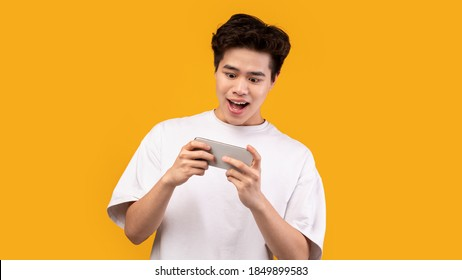 Great App. Portrait of excited joyful asian teen playing mobile video games online on cellphone isolated over orange studio background, copy space. Emotional guy watching video, browsing internet