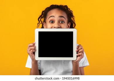 Great Application. Excited Black Girl Holding And Showing Digital Tablet With Empty Screen For Mockup, Covering Face And Mouth, Recommending New App Posing Standing Over Yellow Studio Background