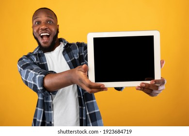 Great Application. Excited Black Guy Showing Tablet Computer With Empty Screen To Camera Recommending New App Posing Standing Over Yellow Studio Background. Digital Tablet Display Mockup For Advert - Shutterstock ID 1923684719