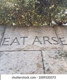 great arsenal text cropped to read eat arse on granite or marble rock