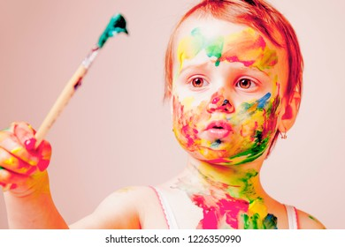 Great artist. Humorous portrait of cute little child girl painting a picture.