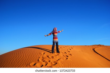 Great barchan with ripple sand and human foot prints and a girl experiencing the joy of traveling at the background of bright blue sky, sunset time in Maranjab desert near Kashan, Iran, Middle East