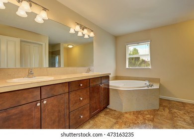 Great bathroom interior with corner bath tub, marble floor, vanity cabinet with two sinks and large mirror. Northwest, USA