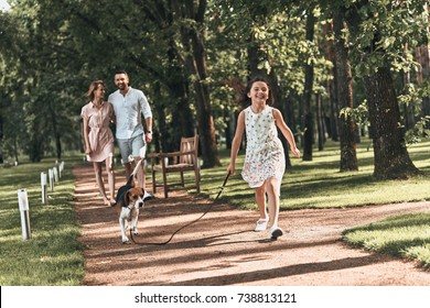 So great to be together! Full length of cute little girl with dog running and smiling while walking with her parents in the park