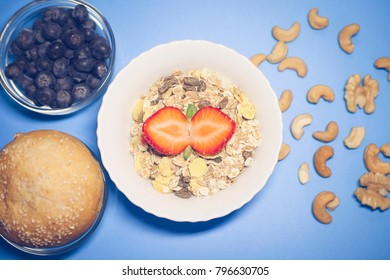 Great breakfast. Berries, fresh pastries and muesli on the blue background. Food concept.