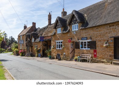 Great Brington, Northamptonshire / UK - May 14th 2019: Picturesque Althorp Coaching Inn and Post Office built from ironstone and partly thatched are popular amenities in the village and beyond.