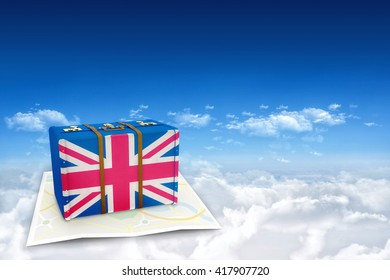 Great Britain flag suitcase against bright blue sky over clouds