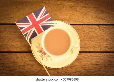 The Great British Cuppa. A cup of tea served in a bone china cup and saucer next to a Union Jack flag on a wooden table.