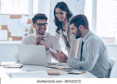 Great business meeting.  Three coworkers discussing something with smile while sitting at the office