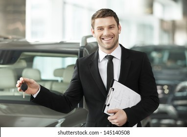 Great choise! Handsome young classic car salesman standing at the dealership holding a key