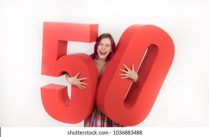 Great Christmas discounts. Emotional and positive beautiful woman with purple hair and in a bright dress, hold in hands a large number, reporting a discount of fifty percent on goods. 50 % off.