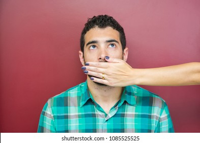 Great concept of female censorship, man with mouth covered by woman's hand.