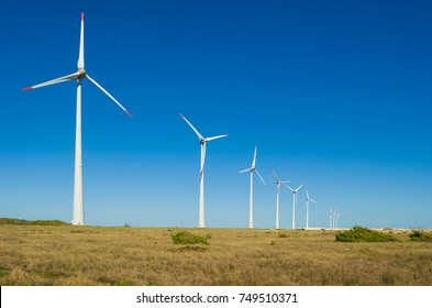 Great concept of renewable, sustainable energy. Wind field with wind turbines, producing aeolian energy under blue sky.