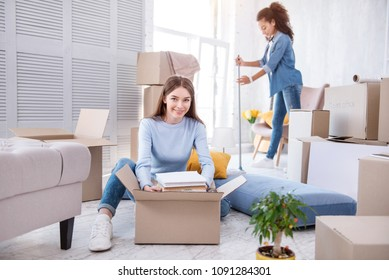 Great cooperation. Cheerful young girl taking a pile of books out of the box while her flat mate cleaning the floor with a mop