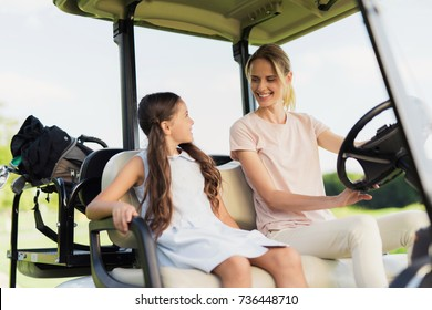 A great day for golf. Mom and daughter in a white golf cart go to play golf.